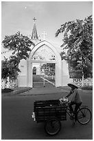 Woman bicycling in front of church. Tra Vinh, Vietnam (black and white)