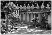 Monk walking past huts, Hang Pagoda. Tra Vinh, Vietnam (black and white)