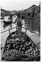 Woman paddles boat loaded with fruits and vegetable, Phung Diem. Can Tho, Vietnam (black and white)