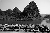 Tour boats and forest-covered limestone rocks, Son Trach. Vietnam (black and white)