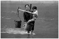 Tay Woman carrying child and water buckets across river. Northeast Vietnam (black and white)