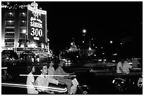 Night traffic in front of a sign celebrating the 300 years of Saigon. Ho Chi Minh City, Vietnam (black and white)