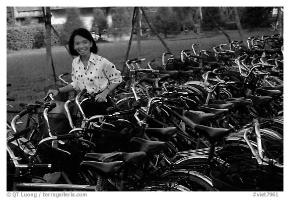 Woman retrieving her bicycle from a bicyle parking area. Mekong Delta, Vietnam