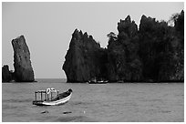 Small boats and offshore rock formations. Hong Chong Peninsula, Vietnam (black and white)