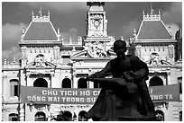 Bronze memorial to Ho Chi Minh by artist Diep Minh Chau and city hall. Ho Chi Minh City, Vietnam ( black and white)