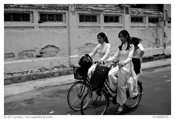 Senior high school girls ride bicycles with impeccable style, wearing elegant Ao Dai uniforms. Ho Chi Minh City, Vietnam