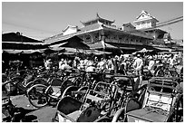 Cyclos wait outside the Bin Tay market in Cholon, district 6. Cholon, Ho Chi Minh City, Vietnam (black and white)