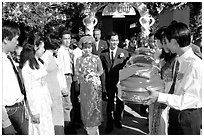 Exchange of gifts at wedding, upon exiting bride's home. The bride traditionaly wears red. Ho Chi Minh City, Vietnam (black and white)