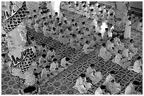 The noon ceremony, attended by priests inside the great Cao Dai temple. Tay Ninh, Vietnam (black and white)