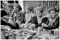 Women sell the colorful garnments after which the Flower Hmong are named. Bac Ha, Vietnam (black and white)