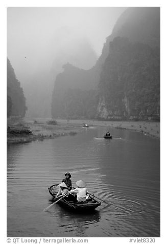Villagers going by boat to their fields, amongst misty cliffs, Tam Coc. Ninh Binh,  Vietnam (black and white)