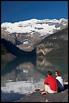 Couple sitting in the sun in front of Lake Louise, morning. Banff National Park, Canadian Rockies, Alberta, Canada