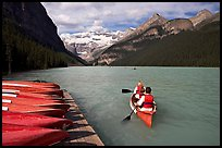 Canoeists paddling out of the boat dock in blue-green waters, Lake Louise, morning. Banff National Park, Canadian Rockies, Alberta, Canada (color)