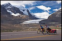 Cyclists on the Icefields Parkway in front of the Athabasca Glacier. Jasper National Park, Canadian Rockies, Alberta, Canada