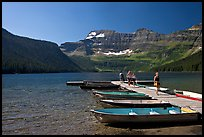 Dock and small boats, with tourists walking down, Cameron Lake. Waterton Lakes National Park, Alberta, Canada ( color)