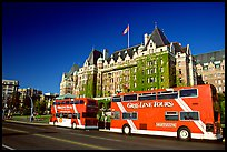 Red double-decker tour busses in front of Empress hotel. Victoria, British Columbia, Canada (color)