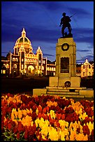 Flowers, memorial statue and illuminated parliament building at night. Victoria, British Columbia, Canada ( color)