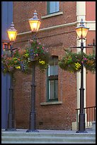 Street lamps with flower baskets and brick wall. Victoria, British Columbia, Canada