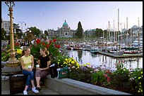 Young Women sitting, Inner harbor. Victoria, British Columbia, Canada ( color)