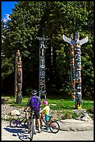 Family with bicycles looking at Totems, Stanley Park. Vancouver, British Columbia, Canada