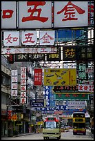 Busses in a street filled up with signs in Chinese, Kowloon. Hong-Kong, China ( color)