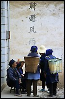 Elderly women with back baskets in front of a wall with Chinese scripture. Shaping, Yunnan, China (color)