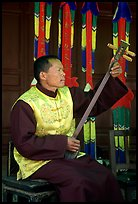 Musician playing a three-stringed traditional moon guitar. Baisha, Yunnan, China ( color)