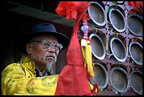 Elderly  musician playing a traditional percussion instrument. Baisha, Yunnan, China ( color)