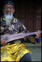 Elderly musician playing the a traditional guitar. Baisha, Yunnan, China ( color)