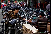 Woman checking out her bicycle at a bicycle lot. Kunming, Yunnan, China ( color)