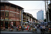 Old wooden buildings, with a high rise in the background. Kunming, Yunnan, China ( color)