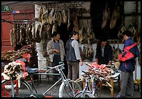 Loading roasted meat on a bicycle. Kunming, Yunnan, China (color)