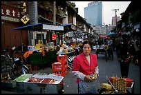 Street market in an old alley of wooden buildings, with a high rise in the background. Kunming, Yunnan, China