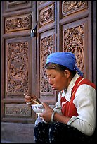 Bai woman eating from a bowl in front of carved wooden doors. Dali, Yunnan, China ( color)