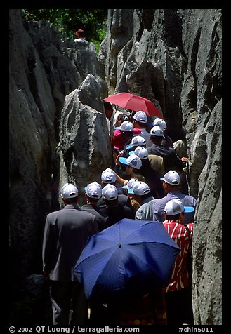 Crowds of Chinese tourists in a walkway among the limestone pillars. Shilin, Yunnan, China (color)