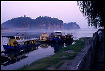 Boats along the river with cliffs in the background. Leshan, Sichuan, China ( color)