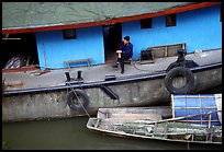 Man sitting on a house boat. Leshan, Sichuan, China ( color)
