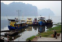 Boats along the river with misty cliffs in the background. Leshan, Sichuan, China ( color)