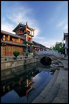 Kegong tower (memorial archway of imperial exam) reflected in canal, sunrise. Lijiang, Yunnan, China ( color)