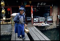 Naxi woman peddling eggs  to local residents walks acros a canal. Lijiang, Yunnan, China (color)
