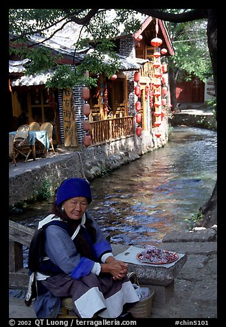 Elderly naxi woman peddles candies near a canal. Lijiang, Yunnan, China