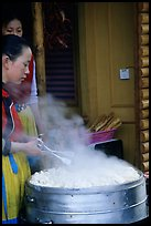 Naxi Women baking dumplings. Lijiang, Yunnan, China