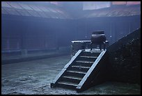 Urn and stairs in courtyard of Xiangfeng temple in fog. Emei Shan, Sichuan, China