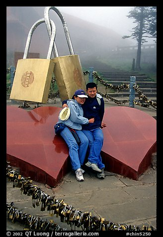 Lovers sit on top of two hearts surrounded by chain locks. Emei Shan, Sichuan, China (color)