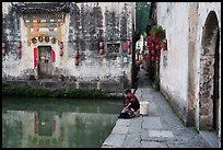 Woman washes laundry in Moon Pond. Hongcun Village, Anhui, China ( color)