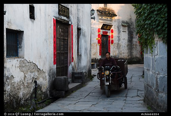 Man driving motobike carriage in narrow street. Xidi Village, Anhui, China (color)