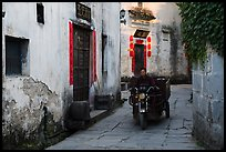 Man driving motobike carriage in narrow street. Xidi Village, Anhui, China ( color)