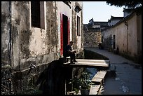 Man sitting in front of house on bridge over stream. Xidi Village, Anhui, China ( color)