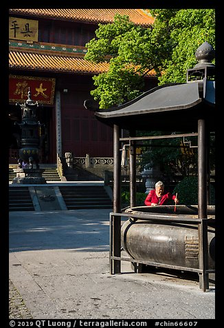 Woman at incense urn, Jingci Temple. Hangzhou, China (color)
