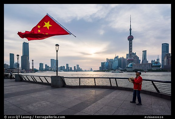 Man flying kite with Chinese flag attached on line, the Bund. Shanghai, China (color)